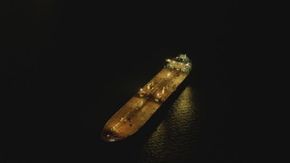 DCA07_149 - 4K stock footage aerial video of flying by oil tanker sailing near Port of Long Beach, tilt to black, California, night