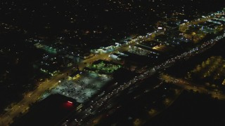 DCA07_179 - 4K stock footage aerial video pan across Highway 101, tilting up, Woodland Hills, California, night