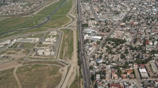 DCA08_046 - 4K stock footage aerial video of following a border highway and fence on the US/Mexico Border, Tijuana