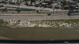 DCA08_062 - 4K aerial stock footage video of a canal by the border fence, Tijuana, Mexico