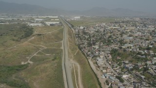 DCA08_065 - 4K stock footage aerial video of following the border fences past urban neighborhoods, US/Mexico Border, Tijuana