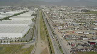 DCA08_069 - 4K stock footage aerial video follow border fence to pass warehouses, US/Mexico Border, Tijuana