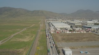DCA08_072 - 4K aerial stock footage video of flying by large warehouses by border fence, US/Mexico Border, Tijuana