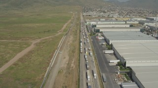 DCA08_073 - 4K stock footage aerial video fly over warehouses and trucks by border fence, US/Mexico Border, Tijuana