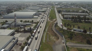 DCA08_084 - 4K stock footage aerial video fly over big rigs, border fence by warehouses, US/Mexico Border, Tijuana