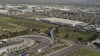 DCA08_094 - 4K stock footage aerial video orbit trucks and warehouses on the US/Mexico Border, Tijuana, Mexico