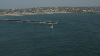 DCA08_156 - 4K stock footage aerial video orbit a sailboat by a breakwater in Mission Beach, California