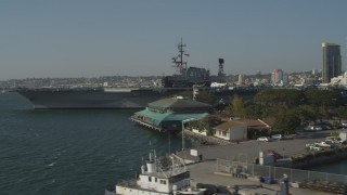 DCA08_196 - 4K stock footage aerial video tilt from fishing boats to reveal an aircraft carrier, the USS Midway, Downtown San Diego, California