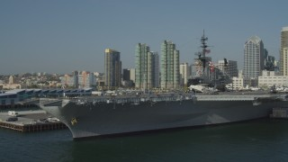 DCA08_197 - 4K stock footage aerial video orbit the docked aircraft carrier, USS Midway, in Downtown San Diego, California