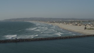 DCA08_229 - 4K stock footage aerial video fly over ocean waves to approach a beach and beachfront homes, Mission Beach, California