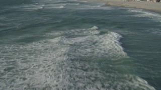 DCA08_230 - 4K stock footage aerial video of flying low over waves rolling toward the beach, Mission Beach, California