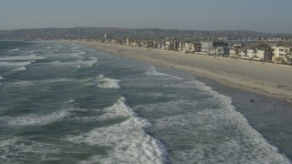 DCA08_231 - 4K stock footage aerial video of flying low over waves rolling toward beach and homes, Mission Beach, California