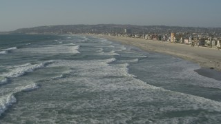 DCA08_232 - 4K stock footage aerial video of flying over waves near beach homes, Mission Beach, California