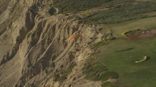 DCA08_254 - 4K stock footage aerial video of orbiting hang gliders on top of cliffs, La Jolla, California