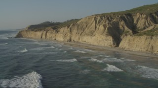 DCA08_255 - 4K stock footage aerial video of flying by waves rolling toward the beach below cliffs, La Jolla, California