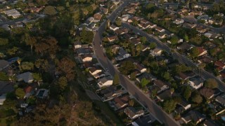 DCA08_275 - 4K aerial stock footage video of a reverse view of tract homes, and reveal the freeway, Bay Ho, California, Sunset