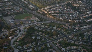 DCA08_283 - 4K stock footage aerial video of suburban tract homes, reveal baseball field, Pacific Beach, California, Sunset