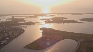 DCA08_288 - 4K stock footage aerial video of flying by an island in a bay, reveal SeaWorld San Diego theme park, California, Sunset