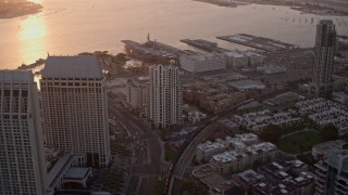 DCA08_303 - 4K stock footage aerial video of flying over downtown skyscrapers to luxury hotel and marina in Downtown San Diego, California, Sunset
