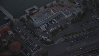 DCA08_320 - 4K stock footage aerial video pan across hotel to reveal seafood company in Downtown San Diego, California, Sunset