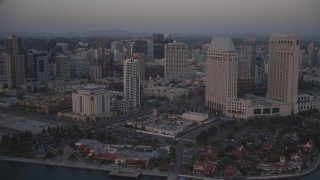 DCA08_321 - 4K stock footage aerial video tilt from seafood company to reveal skyscrapers and hotels in Downtown San Diego, California, Sunset