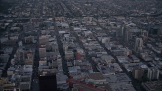 DCA08_324 - 4K stock footage aerial video pan across city skyscrapers, tilt to reveal streets, mall, and park in Downtown San Diego, California, Sunset