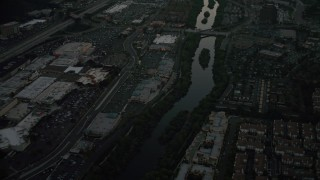 DCA08_334 - 4K stock footage aerial video of a reverse view of a strip mall by the San Diego River, Mission Valley, California, twilight