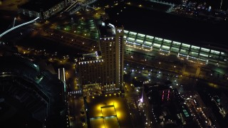 DCA08_350 - 4K stock footage aerial video fly over luxury hotels at night in Downtown San Diego, California, and tilt to reveal Coronado