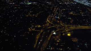 DCA08_351 - 4K stock footage aerial video of tilt from freeway to reveal interchange at night in Downtown San Diego, California