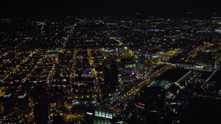 DCA08_363 - 4K stock footage aerial video tilt to reveal luxury hotels, skyscrapers, and city sprawl, Downtown San Diego, California, Night
