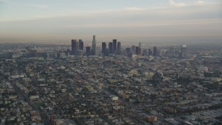 DCLA_013 - 5K stock footage aerial video tilt from heavy traffic on the 101 to reveal the Downtown Los Angeles skyline at sunset, California