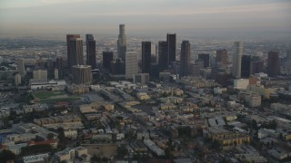 DCLA_015 - 5K stock footage aerial video tilt from Hollywood streets to reveal and approach Downtown Los Angeles skyline at sunset, California