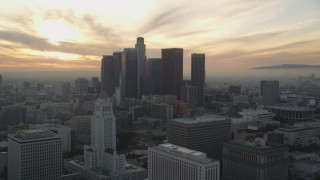 DCLA_031 - 5K stock footage aerial video reverse view of City Hall and Downtown Los Angeles skyline at sunset, California
