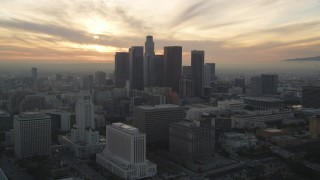 DCLA_035 - 5K stock footage aerial video approach Downtown Los Angeles skyline with setting sun behind clouds, California