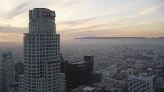 DCLA_049 - 5K stock footage aerial video fly over high-rise to approach US Bank Tower at sunset in Downtown Los Angeles, California