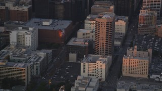 DCLA_054 - 5K stock footage aerial video track police helicopter over Downtown Los Angeles office buildings at twilight, California
