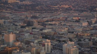 DCLA_055 - 5K stock footage aerial video of tracking police helicopter circling over Downtown Los Angeles at twilight, California