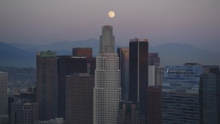 DCLA_071 - 5K stock footage aerial video tilt from rush hour traffic on I-110 to reveal moon over Downtown Los Angeles at twilight, California