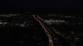 DCLA_098 - 5K stock footage aerial video tilt from highway 118 to reveal and approach shopping center at night in Pacoima, California
