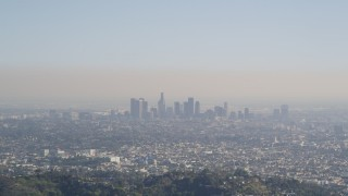 DCLA_107 - 5K stock footage aerial video fly over a green mountain to reveal Downtown Los Angeles skyline, California
