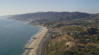 DCLA_132 - 5K stock footage aerial video fly over beach and tilt up Highway 1 in Pacific Palisades, California