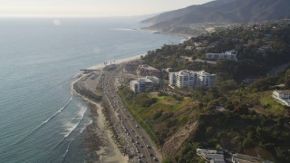 DCLA_135 - 5K stock footage aerial video follow Highway 1 to approach condos in Pacific Palisades, California