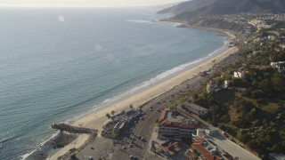 DCLA_136 - 5K stock footage aerial video tilt from Highway 1 to reveal beach in Pacific Palisades, California