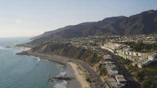 DCLA_137 - 5K stock footage aerial video tilt from Highway 1 and beach to reveal hilltop neighborhoods near ocean in Malibu, California