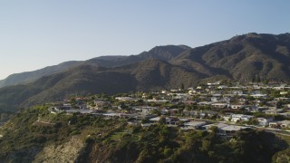 DCLA_138 - 5K stock footage aerial video tilt from Highway 1 to reveal neighborhood  on cliff in Malibu, California