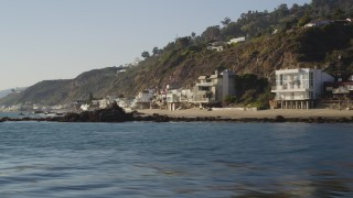 DCLA_143 - 5K stock footage aerial video fly low by beachfront homes in Malibu, California