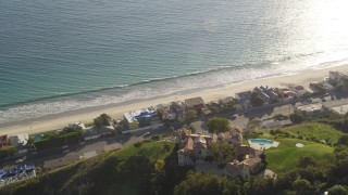 DCLA_152 - 5K stock footage aerial video orbit hilltop mansion to reveal beachfront homes in Malibu, California