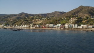DCLA_156 - 5K stock footage aerial video fly low by beachfront homes in Malibu, California