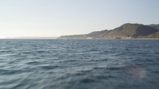 DCLA_159 - 5K stock footage aerial video fly low over the ocean to approach coast of Malibu and tilt to waves, California