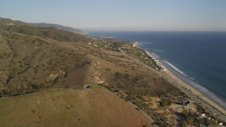 DCLA_166 - 5K stock footage aerial video fly over mountains to reveal and approach Highway 1 on the coast in Malibu, California